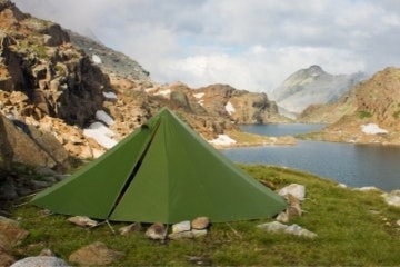 Green tent in alpine landscape with lakes